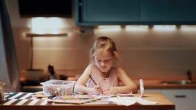 Niña que se sienta en la tabla y que dibuja con la pluma coloreada en sitio grande con la luz suave Nariz conmovedora metrajes