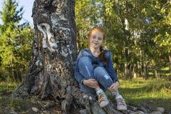 Niña que se sienta en las raíces de un árbol Imagenes de archivo