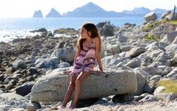 Niña que se sienta en las rocas en el frente de océano en el mar del acantilado del centro turístico de Los Cabos México foto de archivo libre de regalías
