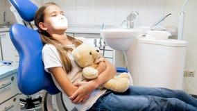 Niña que se sienta en silla del dentista con el oso de peluche del juguete en clínica Fotos de archivo