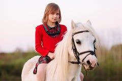 Niña que se sienta en un caballo en un vestido y que mira en la cámara Foto de archivo libre de regalías