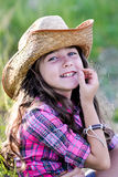 Niña que se sienta en un campo que lleva un sombrero de vaquero Fotografía de archivo