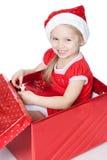 Niña que se sienta en un rectángulo de la Navidad sobre blanco Fotos de archivo libres de regalías