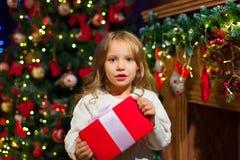 Niña que se sienta por el árbol que sostiene un regalo de la Navidad Imágenes de archivo libres de regalías