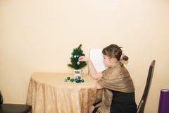 niña que se sienta solamente detrás de la tabla en su sitio y que adorna el pequeño árbol de navidad miniatura Foto de archivo