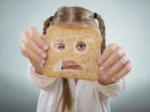 Niña que se sostiene la cara delante de una rebanada de pan triste Imagen de archivo libre de regalías