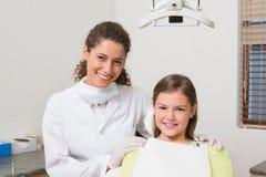 Niña que sonríe en la cámara con su dentista pediátrico Imagenes de archivo