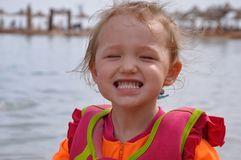 Niña que sonríe en la playa imagenes de archivo