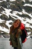 Niña que sonríe haciendo la caminata en las montañas de Hight Foto de archivo