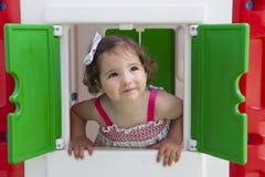 Niña que sonríe a través de la ventana del teatro de los niños Foto de archivo libre de regalías