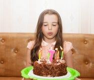 Niña que sopla hacia fuera las velas en una torta de cumpleaños Imagen de archivo