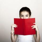 Niña que sostiene el libro rojo Imágenes de archivo libres de regalías