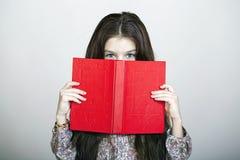 Niña que sostiene el libro rojo Fotografía de archivo