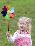 Niña que sostiene el molinillo de viento multicolor en sus manos imagen de archivo