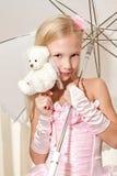 Niña que sostiene el paraguas y que se casa el oso Fotografía de archivo