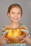 Niña que sostiene la placa de peras amarillas Imagenes de archivo