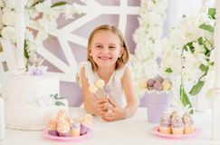 Niña que sostiene las piruletas dulces coloridas en la barra de caramelo Foto de archivo
