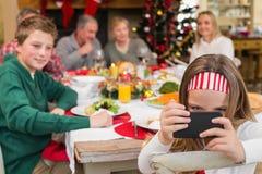 Niña que sostiene smartphone durante cena de la Navidad Imagen de archivo libre de regalías
