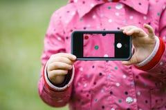 Niña que sostiene un teléfono elegante con la imagen en la exhibición Imagenes de archivo