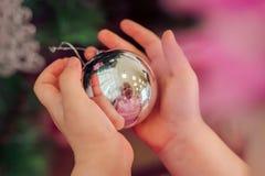 Niña que sostiene una bola de la Navidad Fotografía de archivo libre de regalías