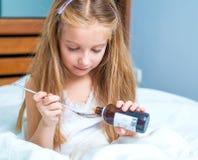 Niña que sostiene una botella del jarabe de la tos Imagen de archivo