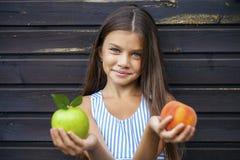 Niña que sostiene una manzana verde y un melocotón Fotografía de archivo
