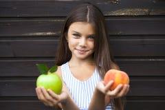 Niña que sostiene una manzana verde y un melocotón Imagenes de archivo