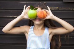 Niña que sostiene una manzana verde y un melocotón Fotos de archivo