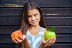 Niña que sostiene una manzana verde y un melocotón Imagen de archivo