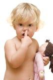 Niña que sostiene una muñeca y selecciones su nariz imagenes de archivo