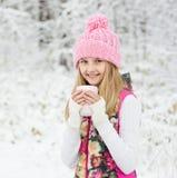 Niña que sostiene una taza de bebida caliente y que sonríe en el fondo Imagen de archivo libre de regalías