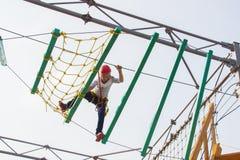 Niña que sube en un curso al aire libre de las cuerdas Foto de archivo