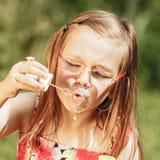 Niña que tiene burbujas de jabón de la diversión que soplan en parque Fotos de archivo libres de regalías