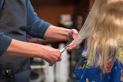 Niña que tiene corte del pelo en el salón fotografía de archivo libre de regalías