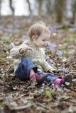 Niña que toca las primeras flores del resorte Imagen de archivo libre de regalías