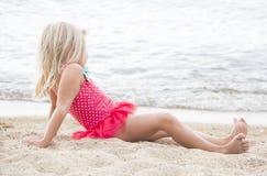 Niña que toma el sol en la playa Imagen de archivo