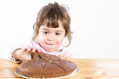 Niña que toma la torta de chocolate hecha en casa Foto de archivo