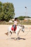 Niña que toma lecciones de montar a caballo de lomo de caballo imagen de archivo libre de regalías