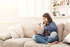 Niña que usa la tableta digital en el sofá en casa Imágenes de archivo libres de regalías