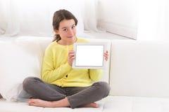 Niña que usa la tableta digital en el sofá en casa Imagen de archivo