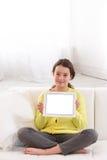 Niña que usa la tableta digital en el sofá en casa Fotografía de archivo