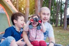 Niña que usa los prismáticos con su familia imagen de archivo libre de regalías