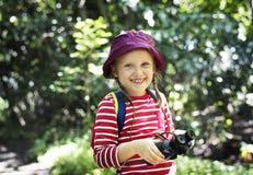 Niña que usa los prismáticos en el bosque Foto de archivo libre de regalías