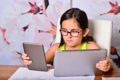 Niña que usa un Tablet PC y un Ebook para la preparación Fotos de archivo libres de regalías