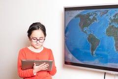 Niña que usa un Tablet PC y una televisión interactiva para la preparación Fotos de archivo libres de regalías