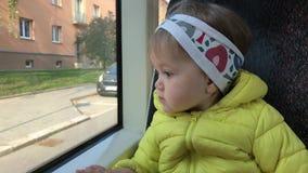 Niña que va por transporte público y que mira hacia fuera la ventana almacen de video