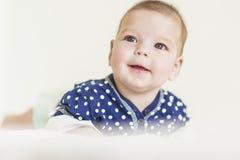 Niña recién nacida caucásica curiosa y sonriente pensativa Imagen de archivo