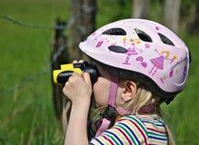 Niña relojes rosados de un casco de la bicicleta que llevan con un par de pequeños prismáticos amarillo-negros imagen de archivo libre de regalías