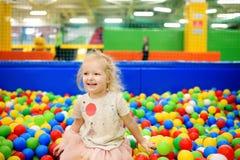 Niña rizada que se divierte en hoyo de la bola con las bolas coloridas Fotos de archivo
