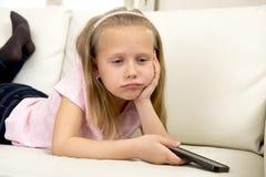 Niña rubia aburrida y cansada en el sofá casero usando Internet app en el teléfono móvil imagenes de archivo